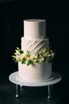 El pastel está decorado con flores en un oscuro.