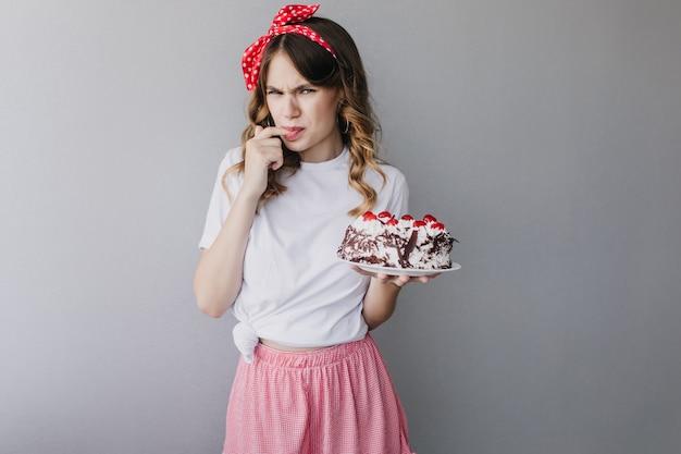 Pastel de degustación de mujer rizada divertida. foto de adorable chica europea con lazo rojo en el pelo.