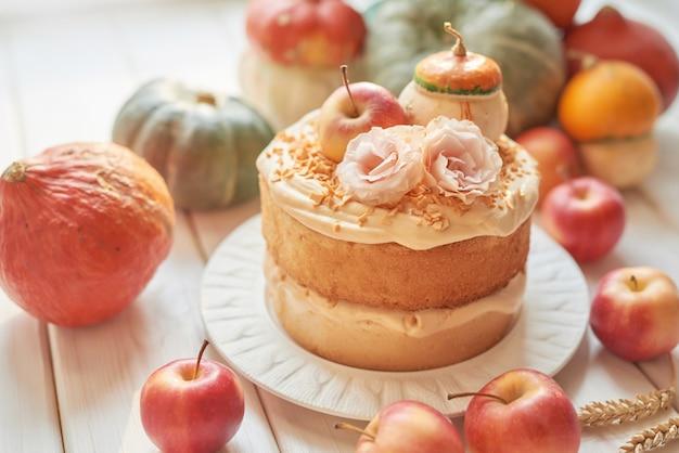 Pastel desnudo de acción de gracias o halloween con calabazas, manzanas y flores