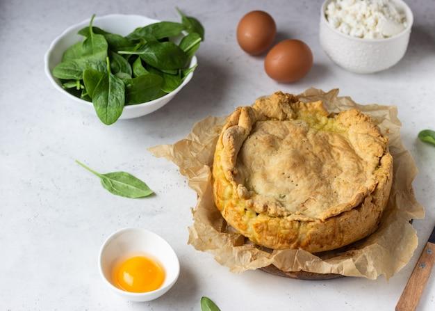 Pastel de espinacas, pollo y ricotta con hojas frescas de espinacas, ricotta y huevo