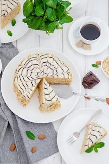Pastel esterhazy tradicional húngaro en un plato blanco con una taza de café, menta y almendras.