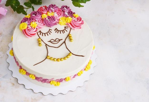 Pastel festivo con flores color crema y una carita de niña en la luz