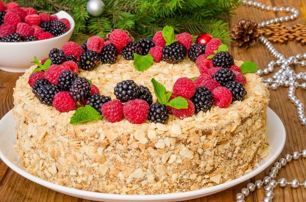 Pastel festivo de napoleón con crema de chocolate y bayas en la parte superior para navidad y año nuevo