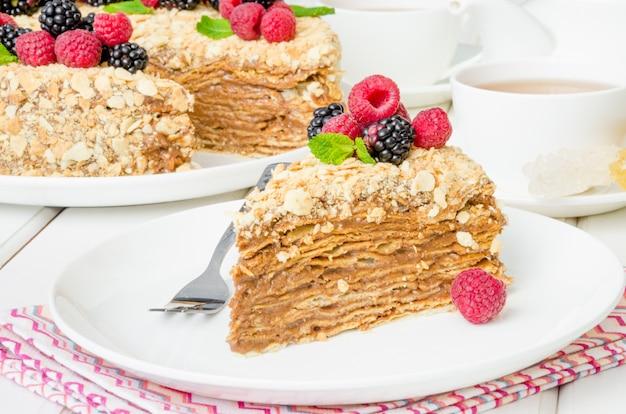 Pastel festivo de napoleón con crema de chocolate y bayas en la parte superior