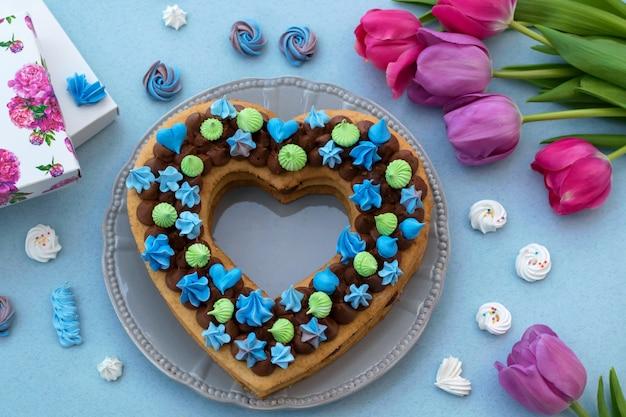Pastel en forma de corazón. día de san valentín o día de la mujer. pastel con merengue azul.