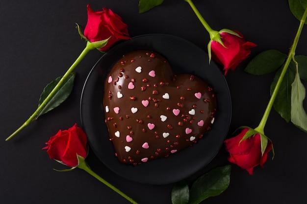 Pastel en forma de corazón y rosa roja para el día de san valentín
