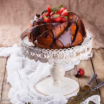 Pastel con fresas y glaseado de chocolate en la base.