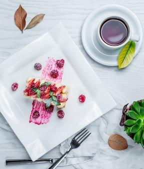 Pastel con fresas y té en la mesa