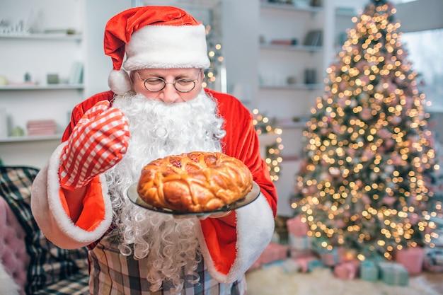 Pastel fresco y sabroso está en manos de santa claus. lo mira y huele. hay un árbol de navidad detrás de él.
