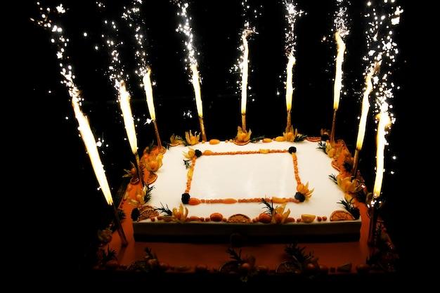 Pastel de frutas de cumpleaños rectangular con velas de fuegos artificiales