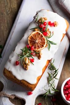 Pastel de frutas espolvoreado con glaseado, nueces, granos de granada y primer plano de naranja seca. pastel casero de navidad e invierno