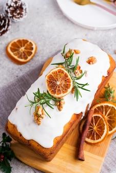 Pastel de frutas espolvoreado con glaseado, nueces y piedra seca de naranja, plano. pastel casero de navidad e invierno