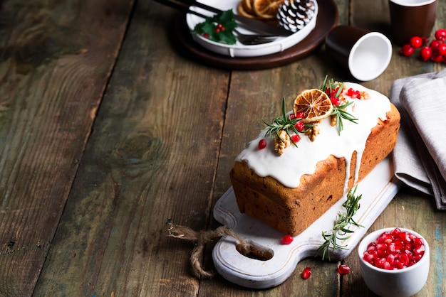 Pastel de frutas espolvoreado con hielo, nueces, granos de granada y naranja seca de madera vieja. pastel casero de navidad e invierno