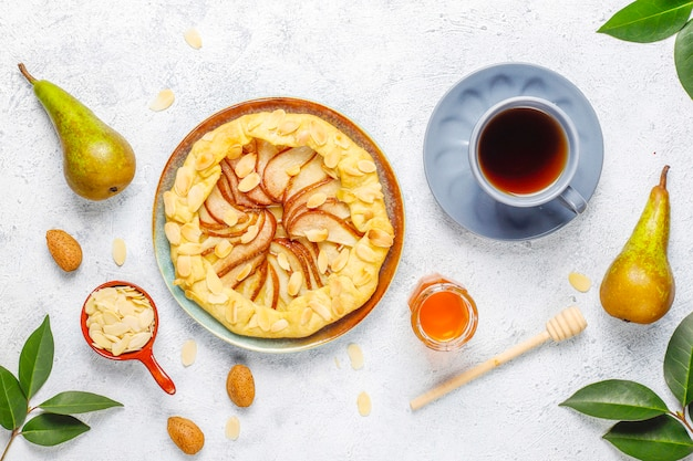 Pastel de galette de pera casero con hojas de almendras y peras verdes maduras frescas