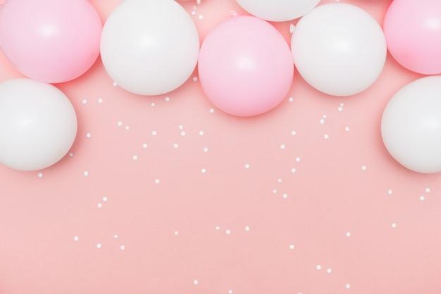 Pastel de globos y confeti blanco sobre rosa.