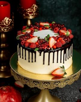 Pastel de goteo de chocolate con pastel blanco adornado con bayas