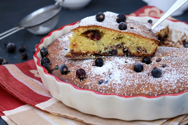 El pastel de grosella negra se encuentra en forma de cerámica con un pedazo de pastel cortado