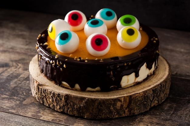 Pastel de halloween con decoración de ojos dulces en mesa de madera