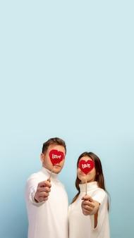 Pastel. hermosa pareja de enamorados sobre fondo azul de estudio. concepto de san valentín, el amor, la relación y las emociones humanas. copyspace. el hombre y la mujer se ven felices juntos.