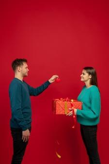 Pastel. hermosa pareja de enamorados sobre fondo rojo de estudio. concepto de san valentín, el amor, la relación y las emociones humanas. copyspace. el hombre y la mujer se ven felices juntos.