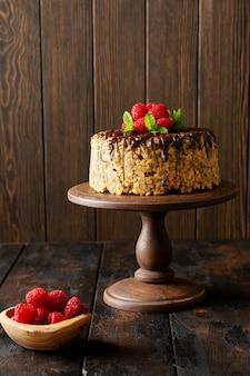 Pastel hormiguero decorado con frambuesas, chocolate y nueces sobre la mesa de madera antigua. enfoque selectivo.