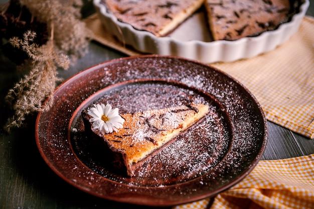 Pastel horneado en forma de cerámica espolvoreado con rodajas de chocolate sobre una mesa de madera.