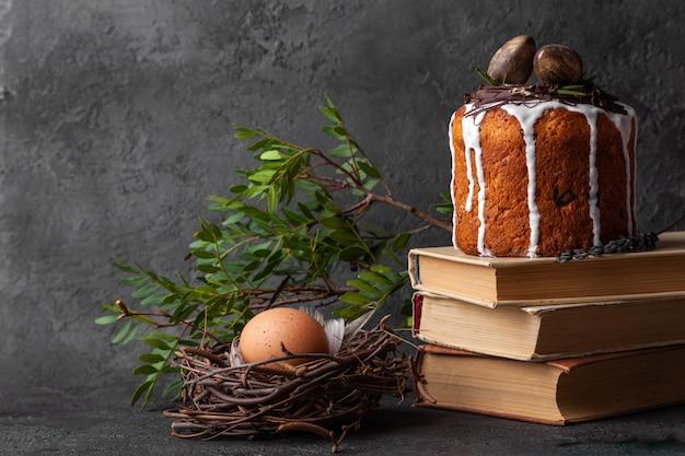 Pastel de kulich de pascua al horno en libros y huevo en nido
