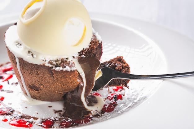 Pastel de lava de chocolate fundido con helado derretido, chocolate con cuchara en plato