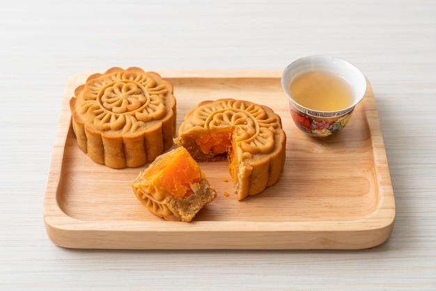 Pastel de luna chino durian y sabor a yema de huevo con té en placa de madera