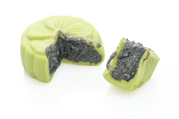 Pastel de luna chino sabor a té verde con sésamo negro aislado sobre fondo blanco.