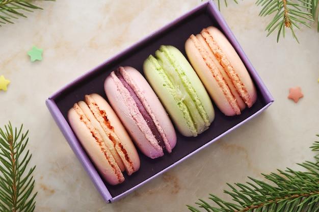 Pastel de macarons en una caja morada con las ramas de un árbol de navidad