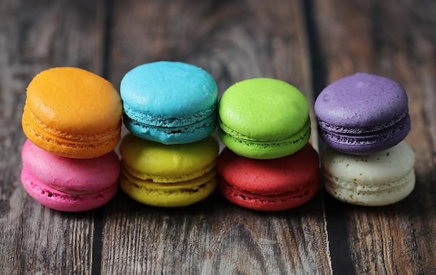 Pastel de macarrones coloridos o macarrones sobre fondo de madera, pequeños pasteles franceses.