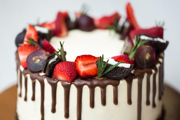 Pastel con manchas de chocolate, fresas, uvas, romero