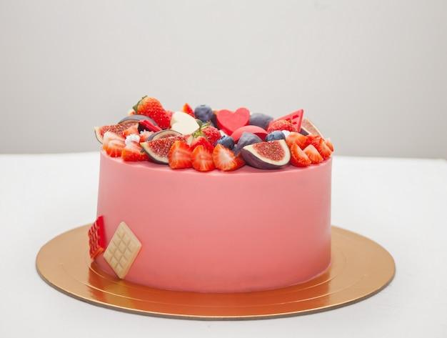 Pastel con manchas de chocolate, frutas y bayas decoradas