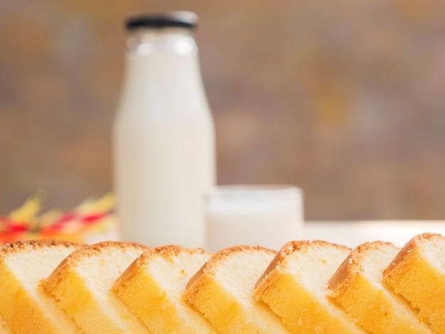 Pastel de mantequilla y botella con vaso de leche en mesa de madera blanca