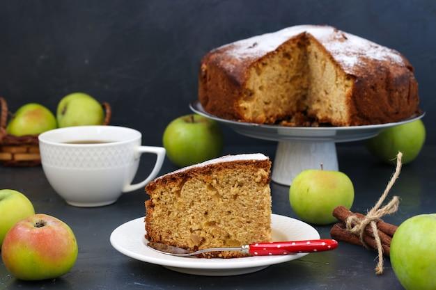 Pastel con manzanas, canela y jengibre en un oscuro con un trozo de pastel y una taza de café en primer plano