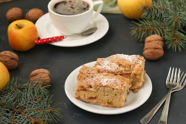 Pastel con manzanas y nueces y una taza de café se encuentra en un plato