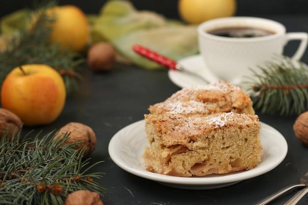 Pastel con manzanas y nueces y una taza de café en un plato oscuro