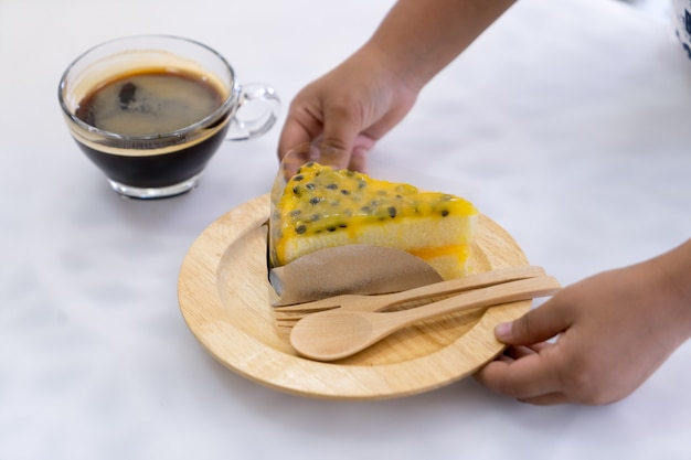 Pastel de maracuyá en plato de madera en mano
