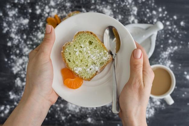 Pastel de menta espolvoreado con azúcar en polvo con mandarinas frescas de naranjas