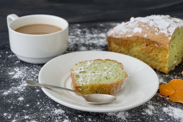 Pastel de menta espolvoreado con azúcar en polvo con una taza de café