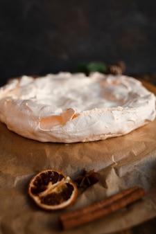 Pastel de merengue desenfocado con canela y cítricos secos
