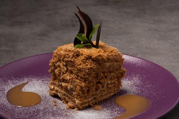 Pastel de miel decorado con chocolate, menta y salsa