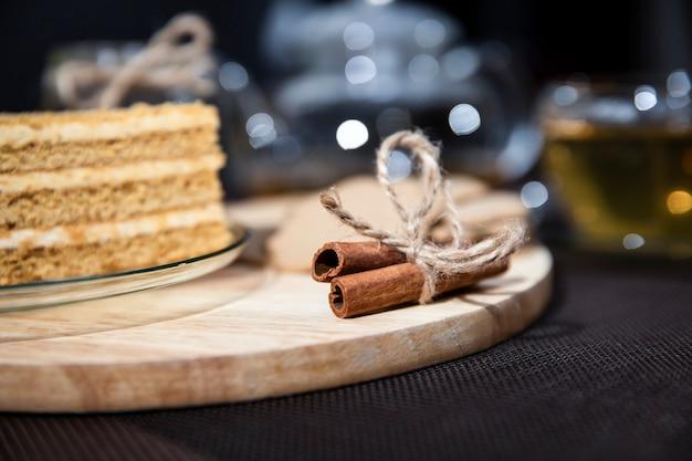 Pastel de miel se encuentra en un plato. té verde en una taza y tetera. la canela está en el tablero.
