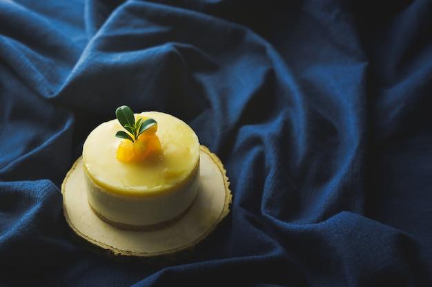 Pastel de mousse de mango decorado con trozos de mango fresco sobre tela azul
