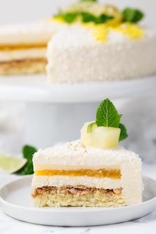 Pastel de mousse tropical decorado, chips de coco, piña y rodaja de limón.