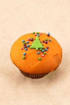 Pastel de muffin de chocolate con glaseado de naranja y decoración navideña. cerrar sobre fondo claro, marco vertical