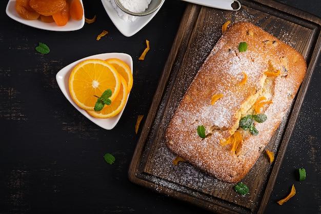 Pastel de naranja con albaricoques secos y azúcar en polvo. vista superior