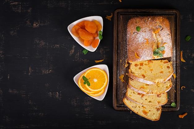 Pastel de naranja con albaricoques secos y azúcar en polvo.