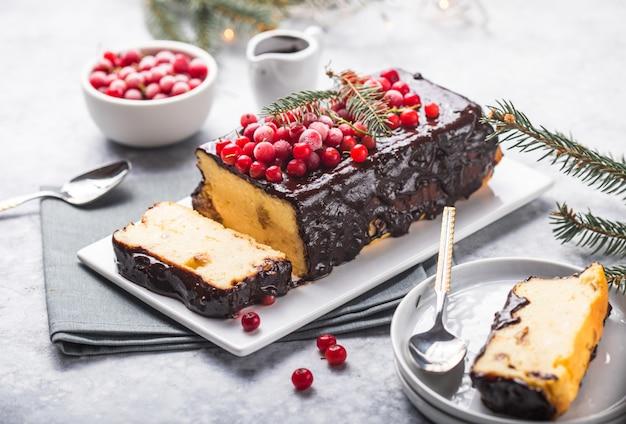 Pastel de navidad con arándanos y adornos navideños en una superficie clara.